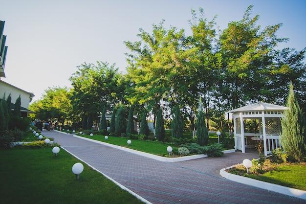 Weiße holzlaube auf der straße in einem grünen park. ein gemütlicher ort, um zeit zu verbringen