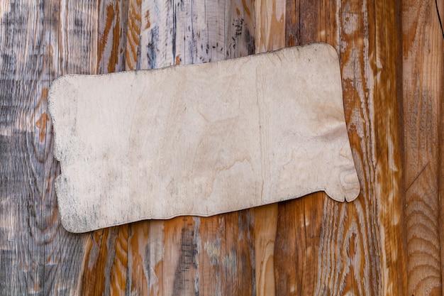 Weiße holzplakette auf holzuntergrund mit ungewöhnlicher textur