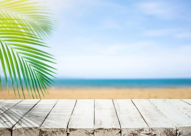Weiße holztischplatte mit verschwommenem meeresstrand und kokosnussblatt