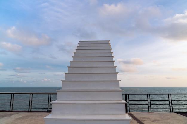 Weiße holztreppe zum himmel auf der terrasse auf dem obersten hügel mit meerblick am abend bei bewölktem himmel, himmelsblick, sonnenschein-aussichtspunkt auf ko proet, chanthaburi, thailand