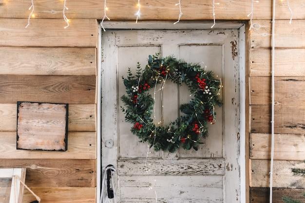 Weiße holztür zum haus mit weihnachtskranz verziert.