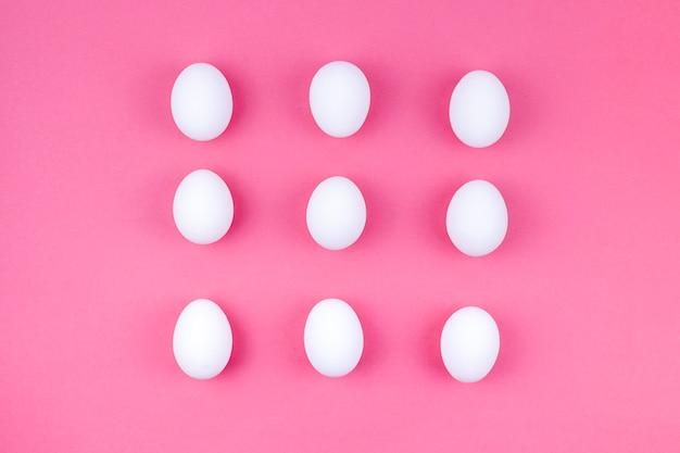 Weiße hühnereien zerstreut auf rosa tabelle