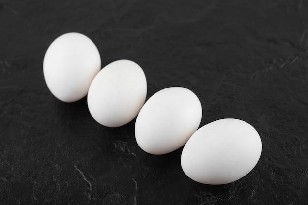 Weiße hühnereier auf einem schwarzen tisch.