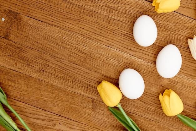 Weiße hühnereier gelbe tulpendekoration frühlingsferienholzhintergrund. hochwertiges foto