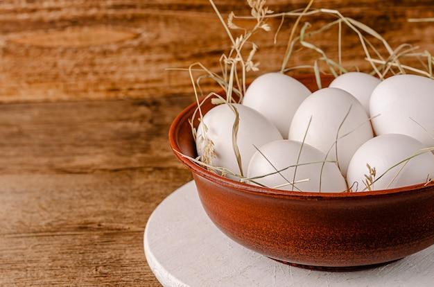 Weiße hühnereier in der schüssel auf rustikalem holztisch