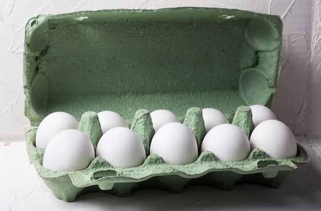 Weiße hühnereier in einem grünen karton, auf einem weißen strukturierten hintergrund mit einem schatten.