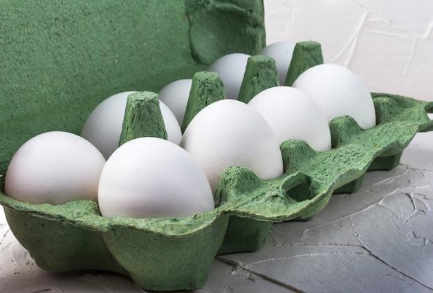 Weiße hühnereier in einem grünen pappbehälter schließen oben auf weiß