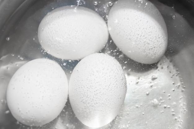 Weiße hühnereier in einem topf kochen.