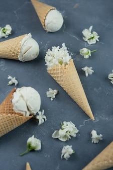 Weiße hyazinthen- und vanilleeiscreme in den waffelkegeln auf blauem hintergrund. muster-konzept