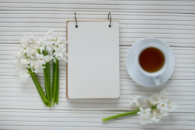 Weiße hyazinthenblume, tasse tee und leeres notizbuch auf einem weißen hölzernen hintergrund des gerillten brettes
