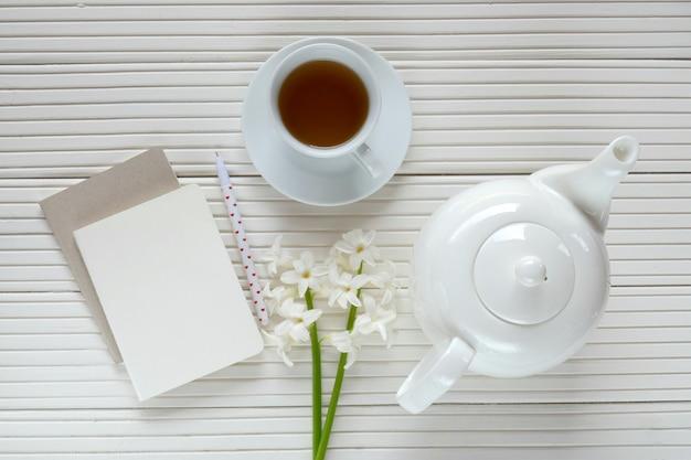Weiße hyazinthenblume, tasse tee, weiße teekanne und leeres notizbuch auf einem weißen hintergrund des hölzernen brettes