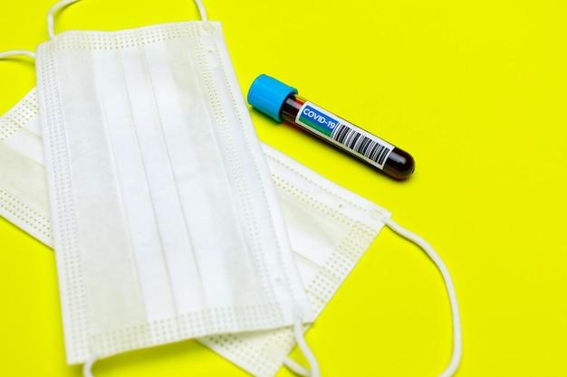 Weiße hygiene-gesichtsmaske und probenblutröhrchenkapsel des covid-19-impfstoffs als notwendige klinische kleidung und apotheke für das gesundheitswesen und starke immunität gegen krankheitsinfektionen durch ausbruch