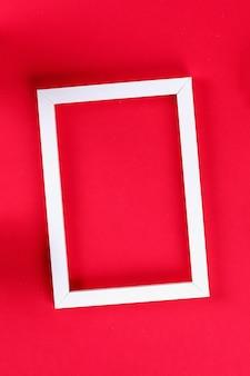 Weiße ideenrahmen des tropischen blattes des sommerideenkonzepts auf rotem hintergrund.