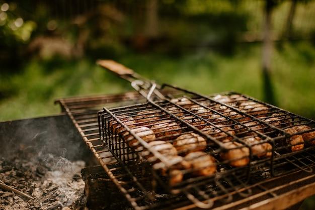 Weiße identische kleine runde champignons in gleichmäßigen reihen in einem grill auf dem grill gestapelt