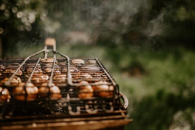 Weiße identische kleine runde champignons in gleichmäßigen reihen in einem grill auf dem grill gestapelt.
