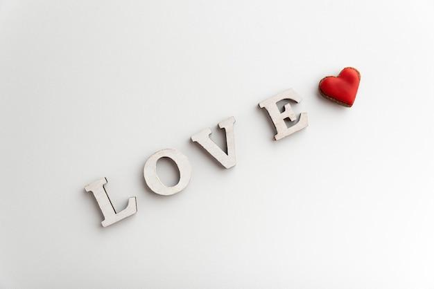 Weiße inschrift liebe auf weißem hintergrund und kleinem rotem herzen. valentinstag.