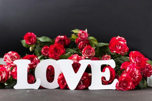 Weiße inschriftenliebe vor dem hintergrund der roten rosen auf beton