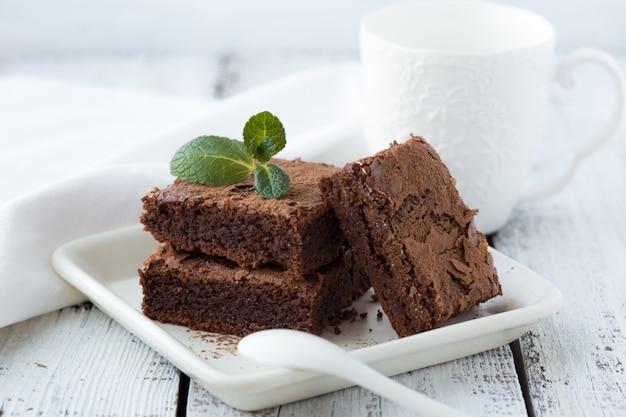 Weiße isolierte wand mit hausgemachten dunklen schokoladenbrownies und minze köstlichen bitteren süßen und fudge. brownie ist eine art von schokoladenkuchen. vintage ton.