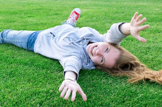 Weiße junge frau der rothaarigen, die auf dem rasen des fußballplatzes und des lächelns liegt und ralaxing ist.