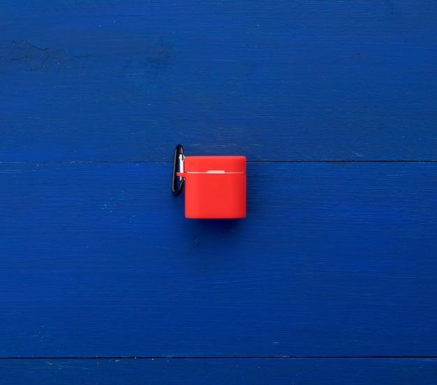 Weiße kabellose kopfhörer, ladebox und rote silikonhülle