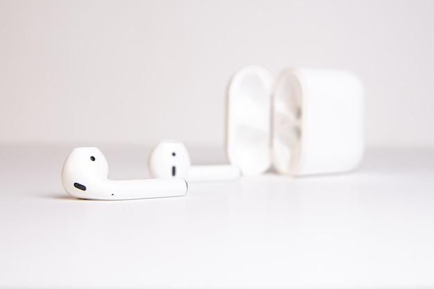 Weiße kabellose kopfhörer mit einer hülle liegen auf einem weißen hintergrund