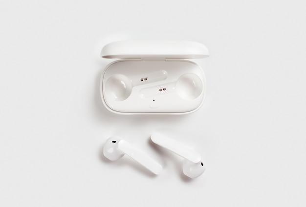 Weiße kabellose kopfhörer mit fall auf draufsicht des weißen hintergrunds