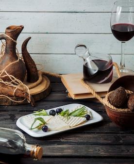 Weiße käsescheiben, garniert mit trauben und estragon, serviert mit rotwein