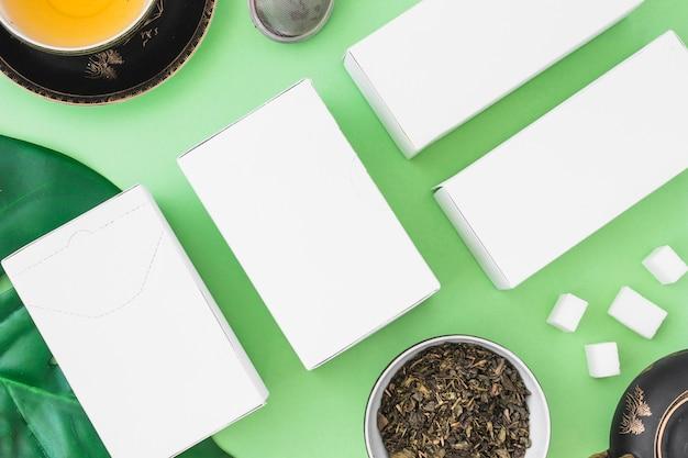 Weiße kästen mit gesundem tee mit kräutern und zuckerwürfeln auf grünem hintergrund