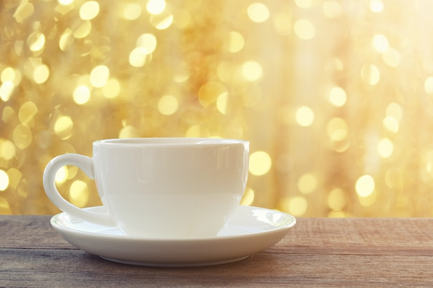 Weiße kaffeetasse auf braunem bretterboden und haben bokeh hellen hintergrund.