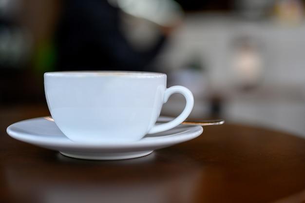 Weiße kaffeetasse auf den schreibtisch gelegt