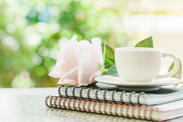 Weiße kaffeetasse auf gewundenen notizbüchern mit rosafarbener blume des süßen rosas