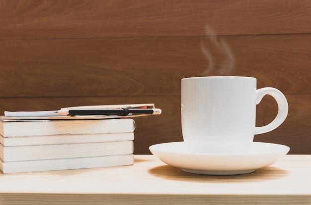 Weiße kaffeetasse auf hölzernem schreibtisch mit bleistift und büchern