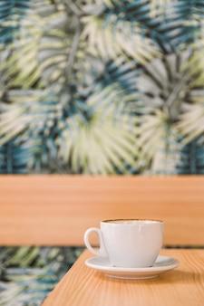 Weiße kaffeetasse auf hölzernem schreibtisch