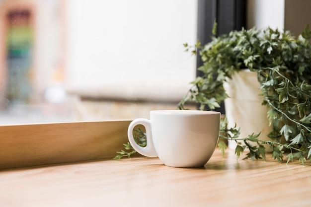 Weiße kaffeetasse auf hölzerner tischplatte