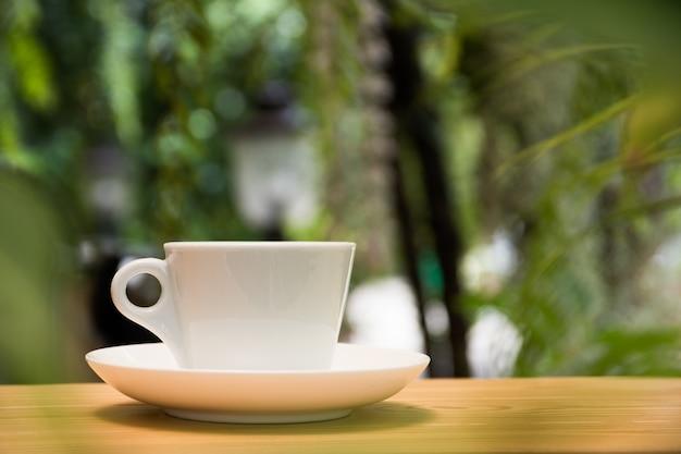 Weiße kaffeetasse auf holztisch im tropischen gartenhintergrund