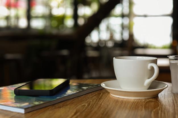 Weiße kaffeetasse auf holztisch mit handy und zeitschrift.