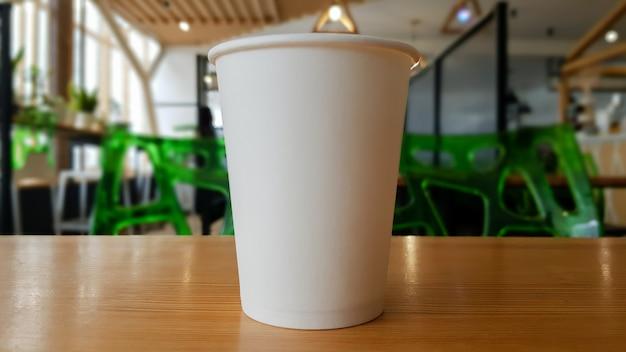 Weiße kaffeetasse aus papier zum mitnehmen oder mitnehmen, auf dem holztisch des cafés oder esszimmers, platz für ein designer-layout. heiße kaffeetasse in einem café.