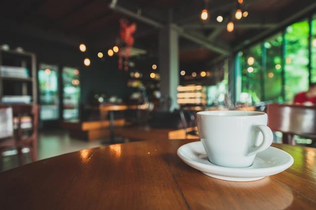 Weiße kaffeetasse der nahaufnahme gelegt auf eine braune hölzerne tabelle in eine kaffeestube