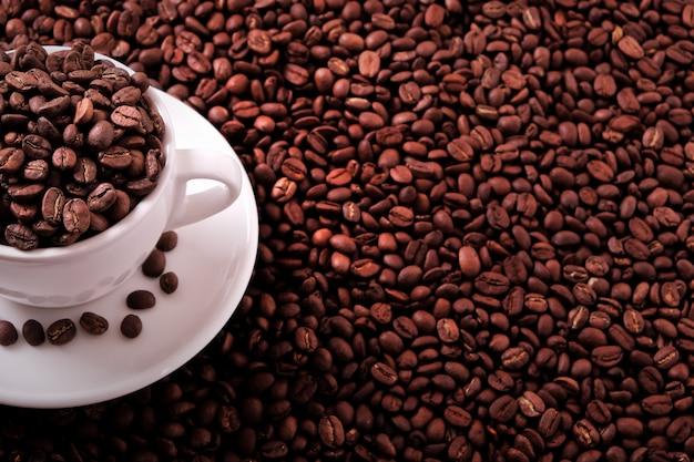 Weiße kaffeetasse gefüllt mit gerösteten bohnen