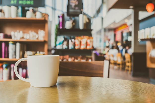 Weiße kaffeetasse im kaffeestube-café - weinlesefilter