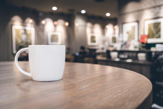 Weiße kaffeetasse im kaffeestubecafé