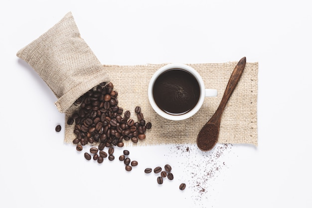 Weiße kaffeetasse, kaffeebohnen, die aus der tasche heraus verschüttet wurden, und holzlöffel mit kaffee