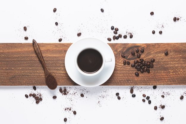 Weiße kaffeetasse, kaffeebohnen verschüttet und holzlöffel mit kaffee