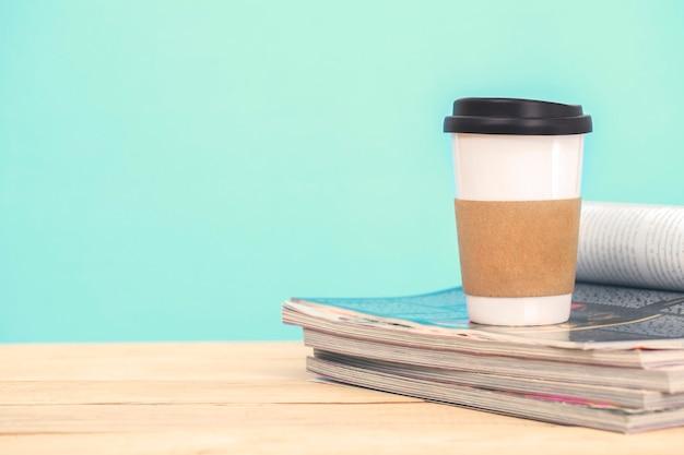 Weiße kaffeetasse mit alter zeitschrift auf holztischweinlesestil