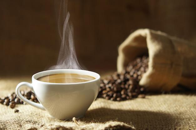 Weiße kaffeetasse mit heißem dampfrauch und röstkaffeebohnen herum