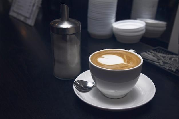 Weiße kaffeetasse mit herzform latte oder cappucino in der kaffeebar.