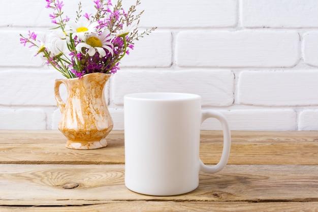 Weiße kaffeetasse mit kamille und lila blumen im goldenen krug