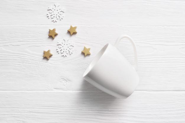 Weiße kaffeetasse mit weihnachtskegeln und -sternen.