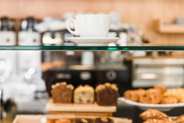 Weiße kaffeetasse über glasschrank im cafégeschäft