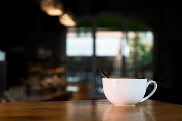 Weiße kaffeetasse über hölzernem schreibtisch in der kaffeestube